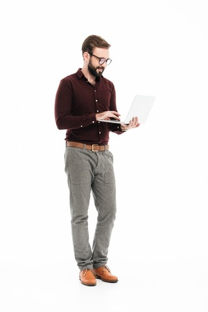 Full length portrait of a confident successful man in eyeglasses using laptop computer while standing isolated over white background