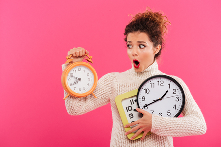 Portrait of a shocked pretty woman holding alarm clocks isolated over pink background