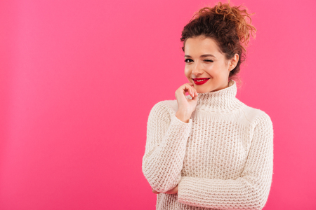 Portrait of a smiling lovely girl looking at camera and winking isolated over pink background
