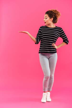 Full length portrait of a pretty young girl holding copy space on her palm isolated over pink background Stock Photo