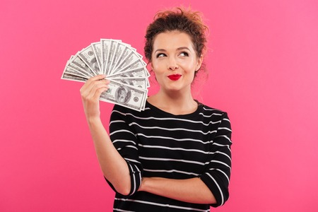 Portrait of a cute smiling girl holding bunch of money banknotes and looking away isolated over pink background Stok Fotoğraf