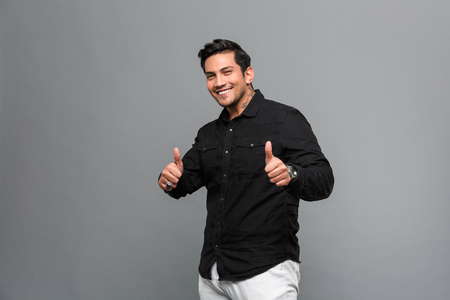 Photo of smiling young handsome man standing isolated over grey wall. Looking camera showing thumbs up.