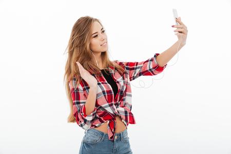 Portret van een gelukkig jong meisje in plaidoverhemd dat een videochat via mobiele telefoon en golvende hand heeft die over witte achtergrond wordt geïsoleerd
