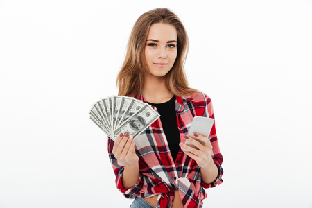 Portrait of a satisfied smiling girl in plaid shirt holding mobile phone and bunch of money banknotes isolated over white background