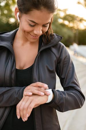Portrait of a happy fitness woman in earphones dressed in sportswear checking her smart watch outdoors
