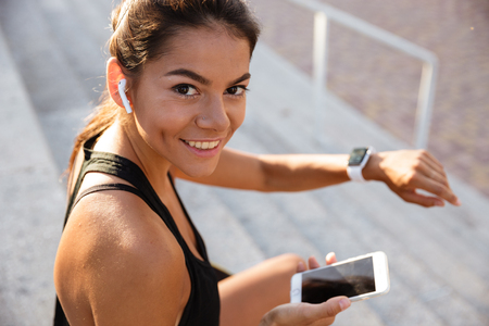 Portrait of a smiling fitness girl in earphones sitting on stairs outdoors with mobile phone and checking her smart watch