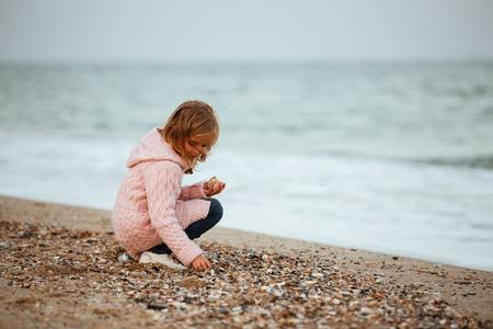Nettes kleines Mädchen , das Felsen am Strand wirft Standard-Bild - 93251161