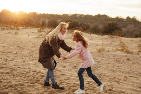 Happy mother playing with her little daughter at the beach