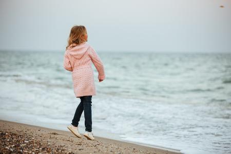 Werfende Felsen des recht kleinen Mädchens am Strand Standard-Bild - 93253092