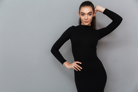 Portrait of a beautiful smiling woman in black dress posing while standing and looking at camera isolated over gray background Banco de Imagens