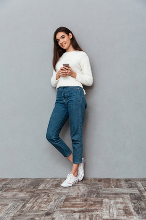 Full length portrait of a smiling pretty girl holding mobile phone while standing and looking away isolated over gray background