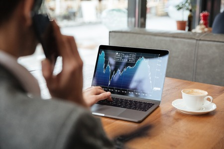 Cropped image of business man sitting by the table in cafe and analyzing indicators on laptop computer while talking by smartphone