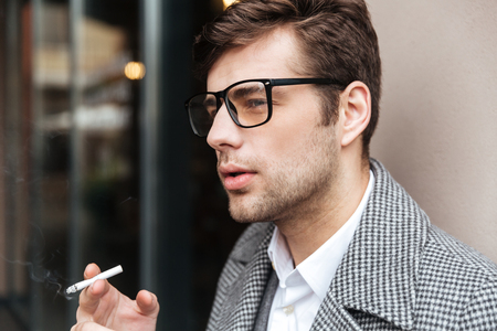 Close up side view of Serious business man in eyeglasses and coat smoking cigarette outdoors