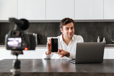 Concentrated young man filming his video blog episode about new tech devices while sitting at the kitchen table and showing blank screen of mobile phone