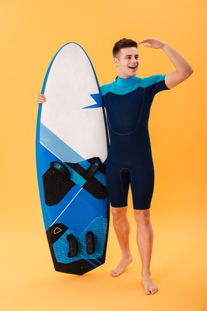 Full length photo of young handsome man in swimsuit holding surfboard while staring into the distance, isolated on yellow background