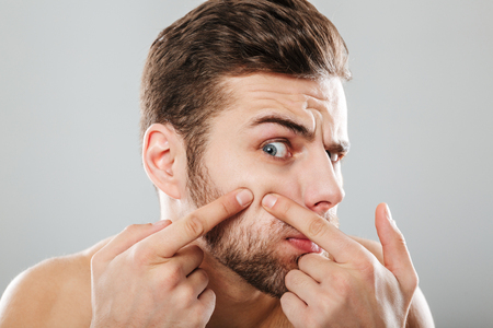 Close up portrait of a man squeezing pimples on his cheek isolated over gray background