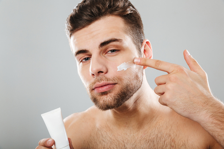 Beauty portrait of a young half naked man applying face cream isolated over gray background