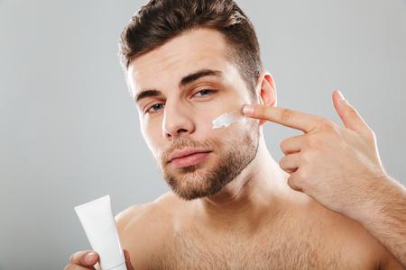 Schoonheidsportret van een jonge half naakte mens die gezichtsroom toepast die over grijze achtergrond wordt geïsoleerd