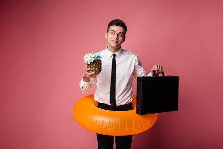 Young businessman in swimming circle holding brief-case and cocktail and dreaming about rest isolated Standard-Bild - 93531371