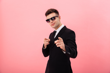 Confident businessman in sunglasses pointing at camera while standing isolated over pink