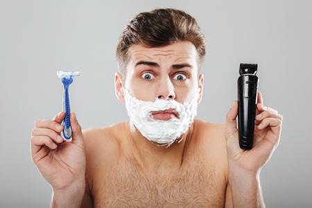 かみそりを持つ彼の顔に剃った泡を持つ混乱した男の肖像画をクローズアップし、灰色の背景の上に隔離されたトリマーの肩を肩をすくめる