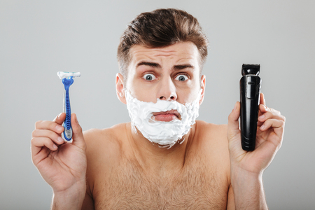 Close up portrait of a confused man with shaving foam on his face holding a razor and a trimmer shrugging shoulders isolated over gray background