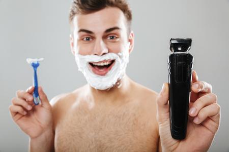 かみそりと灰色の背景の上に隔離されたトリマーを持つ彼の顔に剃る泡を持つ陽気な男の肖像画をクローズアップ