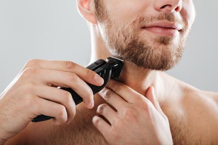 灰色の背景の上に隔離されたトリマーでひげを剃る笑顔の男の肖像画をクローズアップ