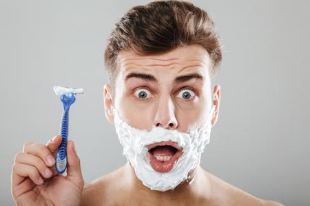 灰色の背景の上に隔離されたかみそりを示す彼の顔に剃る泡を持つ興奮した男の肖像画をクローズアップ