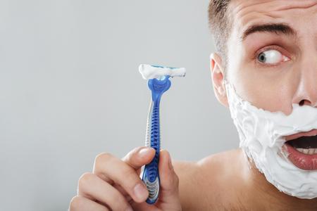 灰色の背景の上に隔離されたかみそりを示す彼の顔に剃る泡を持つ若い男の肖像画をクローズアップ