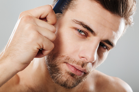 Close up portrait of a handsome man combing his hair isolated over gray background Stock Photo