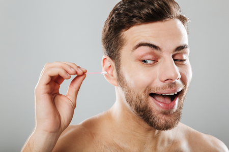Close up portrait of a cheery man cleaning his ears with a cotton swab isolated over gray background