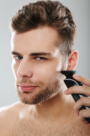 Closeup picture of good-looking adult guy grooming his face with shaving his cheek, using electric shaver over grey wall Banco de Imagens