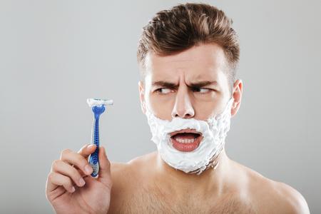 灰色の背景の上に隔離されたかみそりを示す彼の顔に剃る泡を持つ混乱した男の肖像画をクローズアップ 写真素材