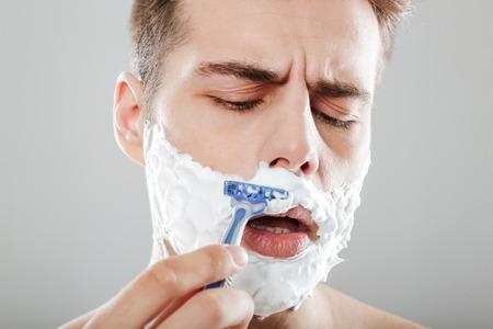 灰色の背景の上に隔離されたかみそりで顔を剃る泡を持つ集中した男の肖像画をクローズアップ 写真素材
