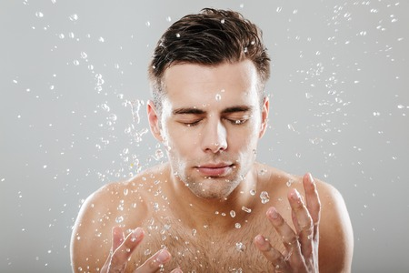 Schließen Sie herauf Porträt eines jungen halb nackten Mannes, der durch die Wassertropfen umgeben wird, die sein Gesicht waschen, das über grauem Hintergrund lokalisiert wird
