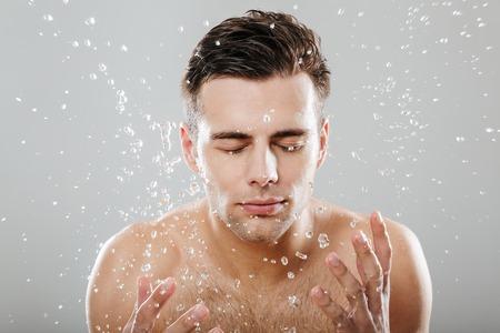 Sluit omhoog portret van een jonge half naakte mens die door waterdalingen wordt omringd die zijn gezicht wassen die over grijze achtergrond wordt geïsoleerd