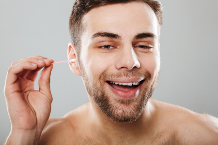 Close up portrait of a smiling man cleaning his ears with a cotton swab isolated over gray background
