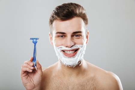 Positive emotions of young attractive guy during shaving with razor in bathroom putting cream on face, over grey background Imagens