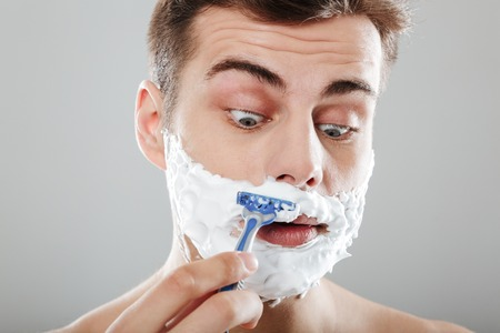 Close up portrait of a young man with shaving foam on his face shaving with a razor isolated over gray background