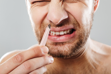Cropped image of a frowning man in pain removing nose hair with tweezers isolated over gray background