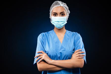 Ernster Doktor in der medizinischen Maske und in der Kappe , die Kamera hält und faltete sich über Schwarzem lokalisiert wird Standard-Bild