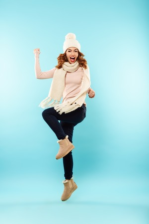 Full length portrait of a cheery young girl dressed in hat and scarf celebrating and jumping isolated over blue background Stock Photo