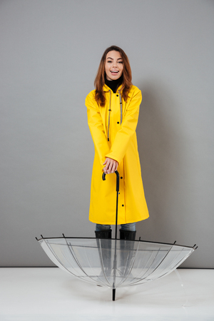 Full length portrait of a smiling girl dressed in raincoat and rubber boots posing while standing with an open umbrella isolated over gray background