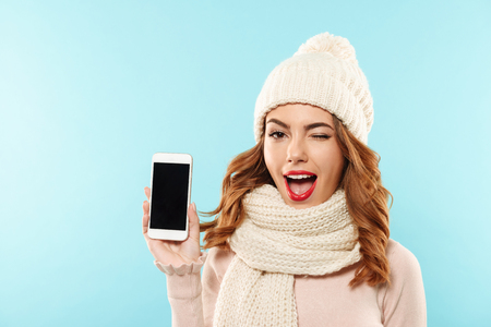 Close up portrait of a happy playful girl dressed in hat and scarf showing blank screen mobile phone and winking isolated over blue background