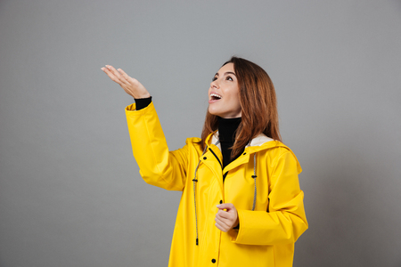 Portrait of an excited girl dressed in raincoat and rubber boots posing while standing with outstretched hand isolated over gray background Banque d'images