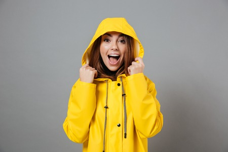 Portrait of a joyful girl dressed in raincoat posing with hood on her head and looking at camera isolated over gray background
