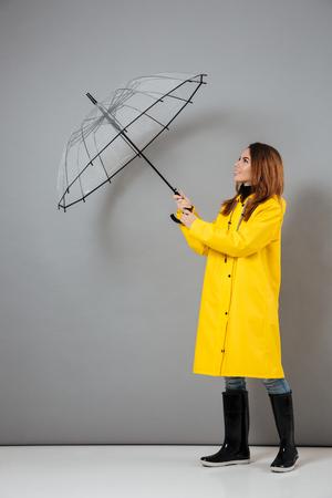 Het volledige lengteportret van een mooi meisje kleedde zich in regenjas en rubberlaarzen die terwijl status met een open die paraplu stellen over grijze achtergrond wordt geïsoleerd Stockfoto