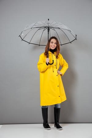 灰色の背景の上に隔離された開いた傘で立っている間、レインコートとゴムブーツに身を包んだ陽気な女の子の完全な長さの肖像画