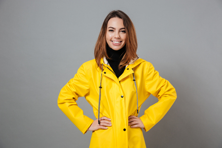 Portrait of a happy girl dressed in raincoat posing while standing with hands on hips isolated over gray background Stockfoto